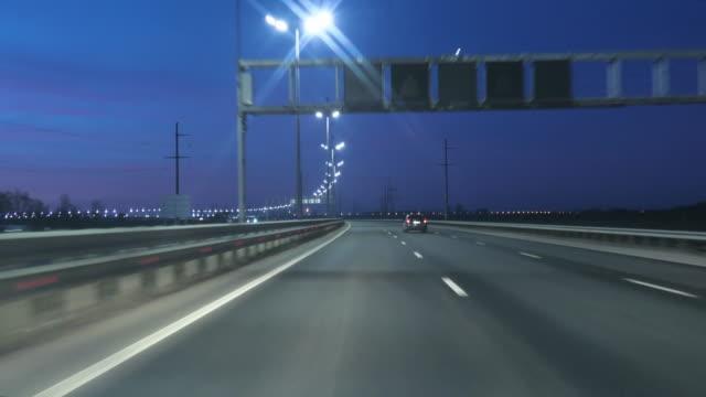 vidéos et rushes de conduite de voiture pov sur l'autoroute dans la nuit avec peu de trafic après le coucher du soleil. soirée sunset street lights. nuit, caméra en face, référence pare-brise. conduite de voiture sur l'autoroute à la foncée 4k pov. - autoroute