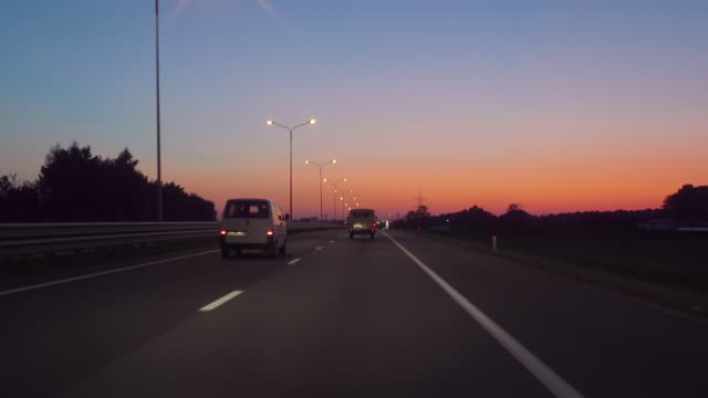 driving car on highway at dark 4k pov. evening sunset street lights. night, camera in front, windshield reference. driving car pov on freeway in of night in with little traffic after sunset. - luce stradale video stock e b–roll