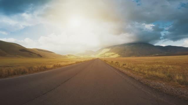 在日落時分在直路上行駛汽車的角度來看 - 路 個影片檔及 b 捲影像