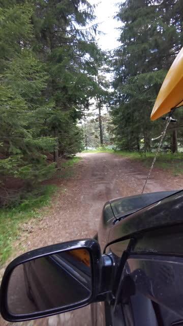 fahren auto mit gelbem kajak auf der landstraße, fahrersicht. lokale roadtrip. - kieferngewächse stock-videos und b-roll-filmmaterial