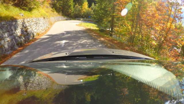 vidéos et rushes de conduite sur une route de montagne sinueuse à travers forêt d'automne - pare brise