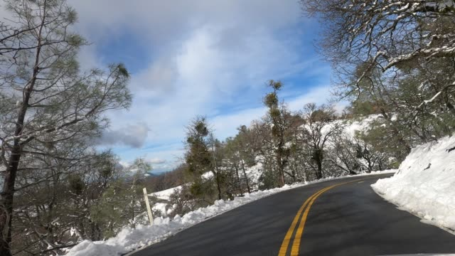 Driving down from the top of Mount Hamilton, on a sunny winter day with fresh snow covering the mountain slopes; South San Francisco Bay Area, California
