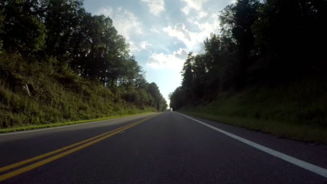 Driving Down Straight Counrty with Sun Flair Low angle view of riding down a two lane straight country road with clouds and blue sky  and the sun shining through the treetops country road stock videos & royalty-free footage
