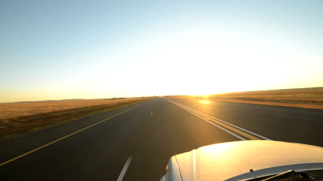 Driving down two lane highway through beautiful and sparse South African landscape at sunset video