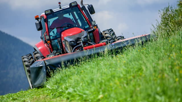 Driving downhill and using a gras cutting machinery to help him cut grass