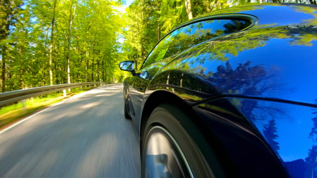 Driving fast with a sports car on a winding country road surrounded by lush foliage Driving an elegant and luxurious blue sports car on an empty country road through picturesque scenery on a beautiful sunny day, view from the side, surrounded by lush foliage sports car stock videos & royalty-free footage
