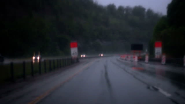 Driving into construction zone during chaotic thunderstorm - POV angle Driving into construction zone during chaotic thunderstorm - POV angle environmental consciousness stock videos & royalty-free footage