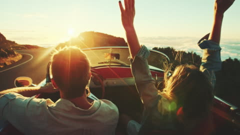 Driving Into the Sunset Happy couple driving on country road into the sunset in classic vintage sports car enjoyment stock videos & royalty-free footage