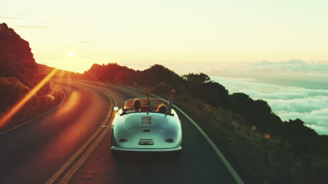 Driving Into the Sunset Happy couple driving on country road into the sunset in classic vintage sports car holiday stock videos & royalty-free footage