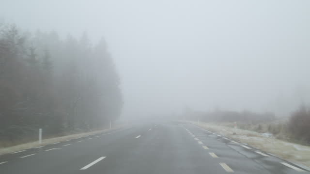 Driving on a country road on a foggy winter day - POV shot - hand held camera