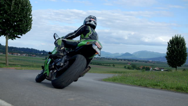 Driving on a country road on a motorcycle A motorcyclist is driving on a country road away from the camera. Close-up shot. The day is sunny and bright. The motorcyclist is dressed in green and black. motorcycle stock videos & royalty-free footage