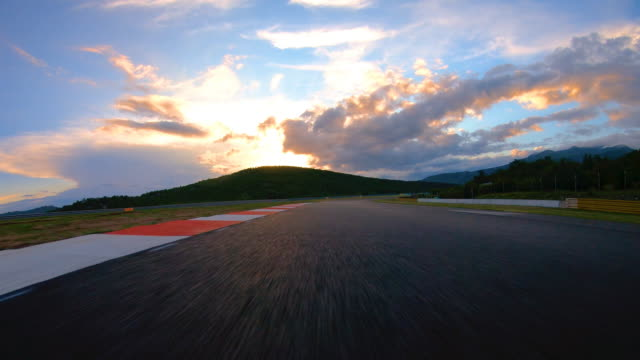 Driving on a race track at sunrise Driving fast on a race track, illuminated by the light of a rising sun angle stock videos & royalty-free footage