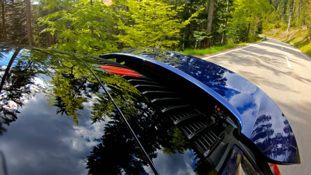 driving on a scenic winding road surrounded by green trees, view of rear windshield, tail lights and spoiler - spoiler filmów i materiałów b-roll