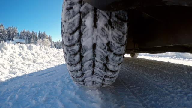 driving on a snowy single lane winter forest road - traccia video stock e b–roll