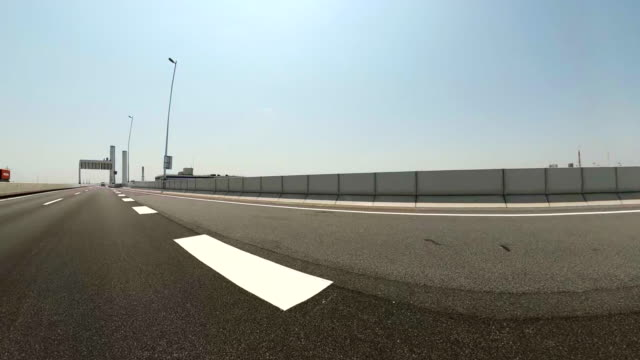 Driving on an empty highway at sunny day / Rear and side view shot from car.