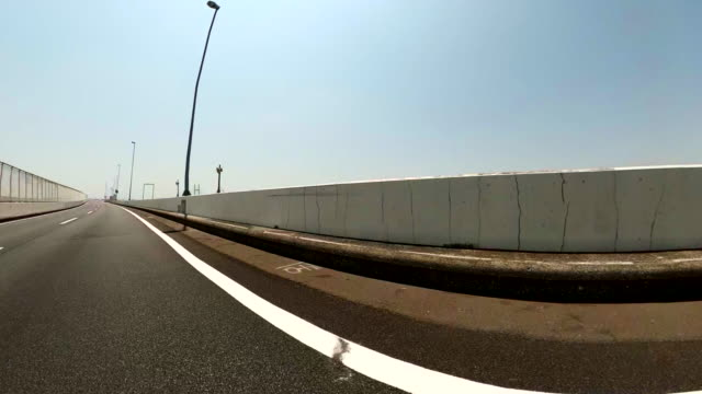 Driving on an empty highway at sunny day / Rear view shot from car.