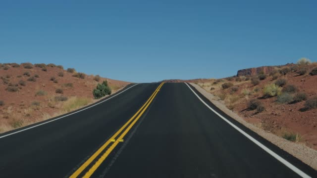 Driving On An Empty Hilly Road Going To The Distance To Red Mountain Rocks
