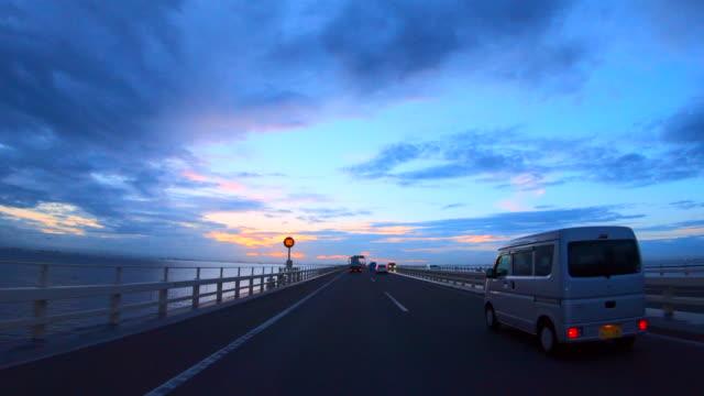 夕暮れ時の橋の上で運転 - 車点の映像素材/bロール