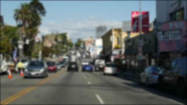 driving on downtown streets of los angeles, california usa. defocused view from car thru glass windshield on driveway. blurred road with vehicles in hollywood. camera inside auto, la city aesthetic - viale video stock e b–roll