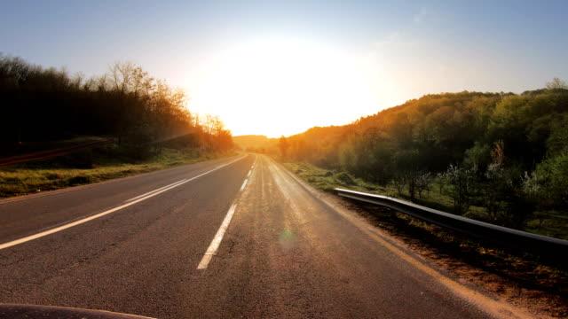 pov fahren auf der autobahn in richtung strahlende sonne bei frühlingssonnenaufgang - horizont stock-videos und b-roll-filmmaterial