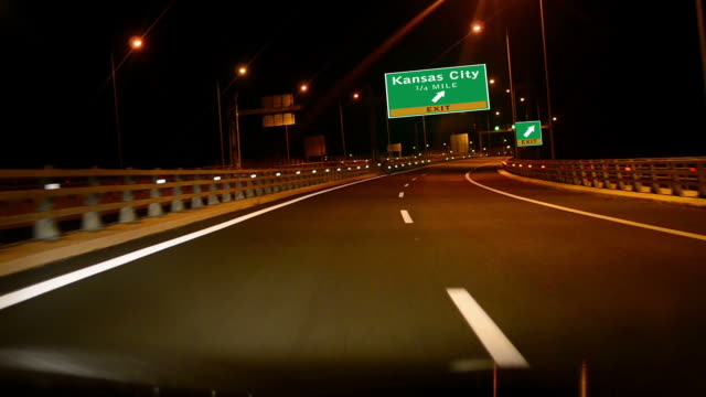 Driving on Highway/interstate at night,  Exit sign of the Kansas City, Missouri video