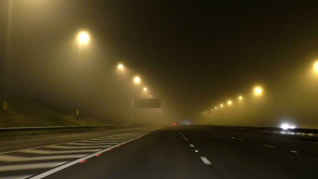 driving on misty motorway at night - droga wielopasmowa filmów i materiałów b-roll