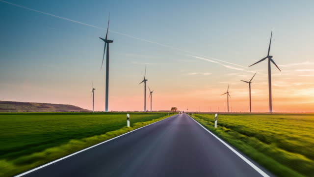 Driving on Road surrounded by Wind Turbines