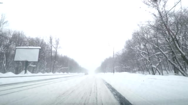 Driving POV on snowy road. Snow storm driving urban street fast timelapse . Winter snow storm hit . Dangerous driving conditions on snow packed and icy roads. video