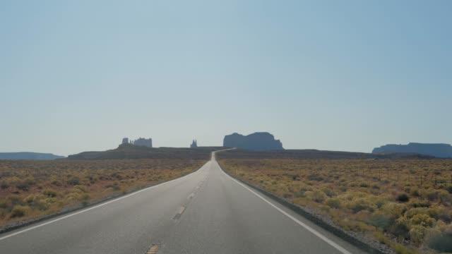 ロックビュートのモニュメントバレーの背景で有名な道路を運転 - 記念建造物点の映像素材/bロール