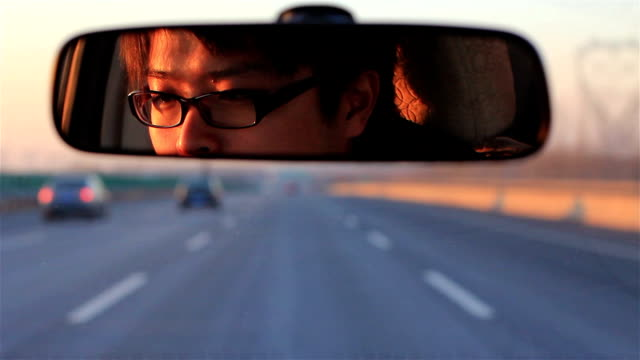 driving on the highway A Chinese man is driving on the highway rear view mirror stock videos & royalty-free footage