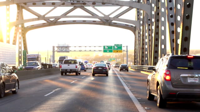 Driving over the busy traffic bridge full of cars and trucks at golden sunset video