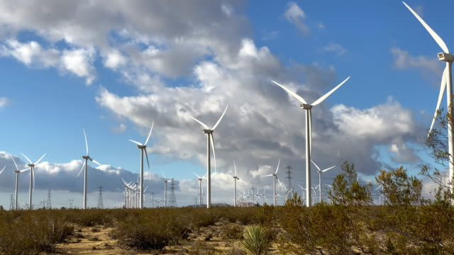 Driving past massive wind turbines in the California desert Driving past massive wind turbines with dramatic clouds in the background. Shot in the Mojave Desert in California. turbine stock videos & royalty-free footage