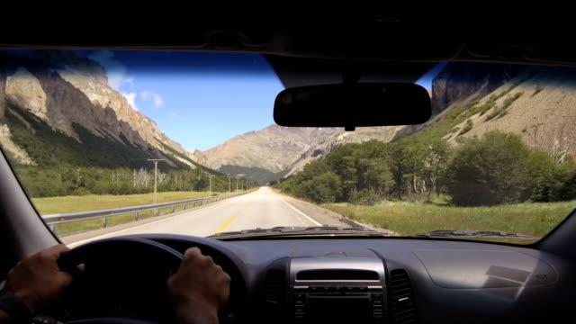 kör plattan. bil på en landsväg, bergskedjan, dal-pov-synpunkt front-vindruta, instrumentbräda, händer, ratt referens. dag. - vindruta bildbanksvideor och videomaterial från bakom kulisserna