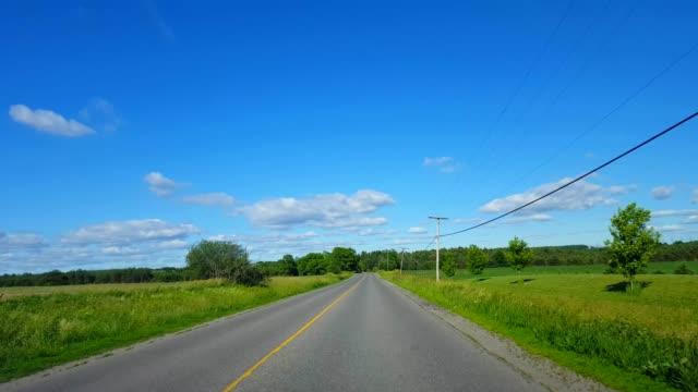 driving rural road along farmland during bright summer day.  driver point of view pov beautiful sunny countryside farm fields. - wiejska droga filmów i materiałów b-roll