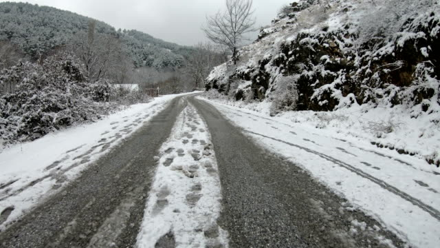 driving slow and cautious on the snowy frozen rural road - traccia video stock e b–roll