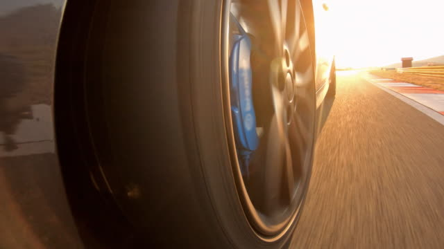 Driving sports car on a race track at sunset