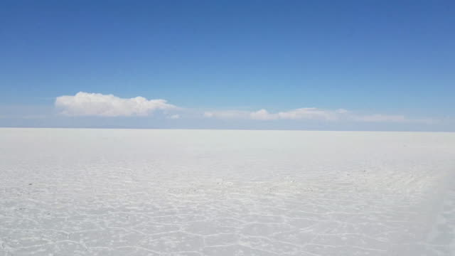 Driving through The Uyuni Salar in Bolivia. White salt flats and a bright blue sky. South America Driving through The Uyuni Salar in Bolivia. White salt flats and a bright blue sky. South America salt flat stock videos & royalty-free footage
