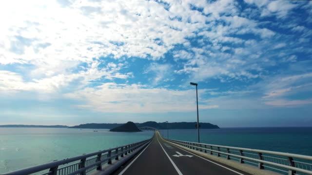driving to a future, tsunoshima bridge over ocean - strada tortuosa video stock e b–roll