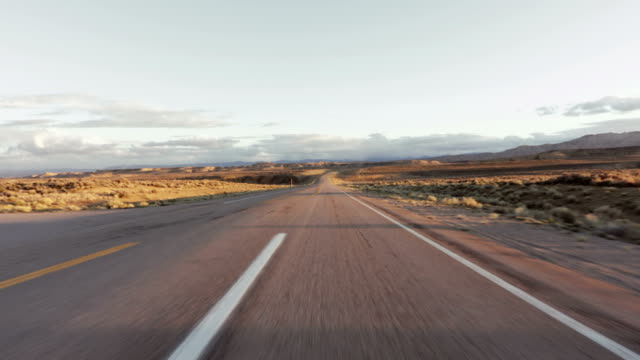 Driving USA: Beautiful point of view shot on long straight road, sunrise/sunset