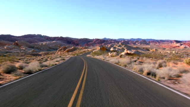 Driving USA: Car driving point of view through beautiful desert landscape on an empty road through the Valley of Fire, Nevada