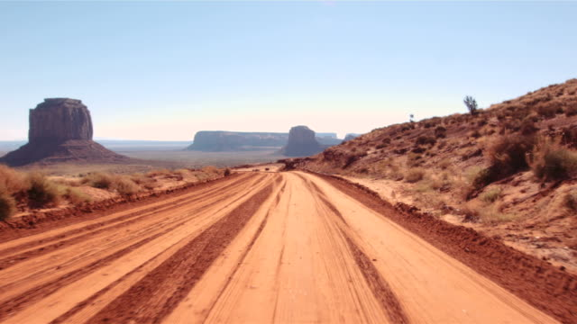 Driving USA: journey along rough dirt road in Monument Valley Utah Arizona Car mount camera driving into the desert through iconic red sandstone rock formations rock formations stock videos & royalty-free footage