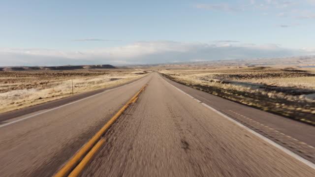 driving usa: spectacular point of view car shot speeding across desert - lungo video stock e b–roll