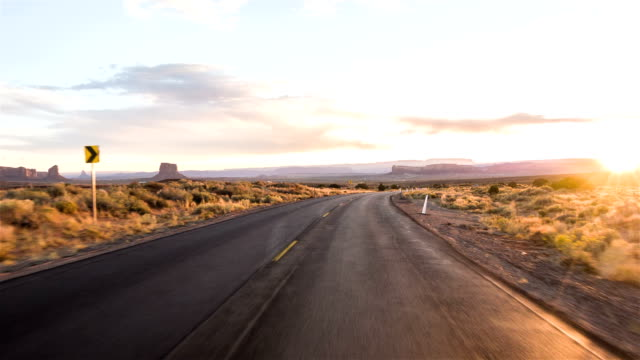 Driving USA: Spectacular sunset driving shot along lonely road in American desert