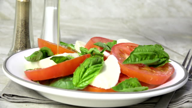 Drizzling olive oil over a Caprese salad