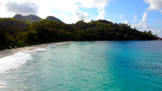 vídeos de stock, filmes e b-roll de dron está voando ao longo da praia, seychelles. - quadricóptero