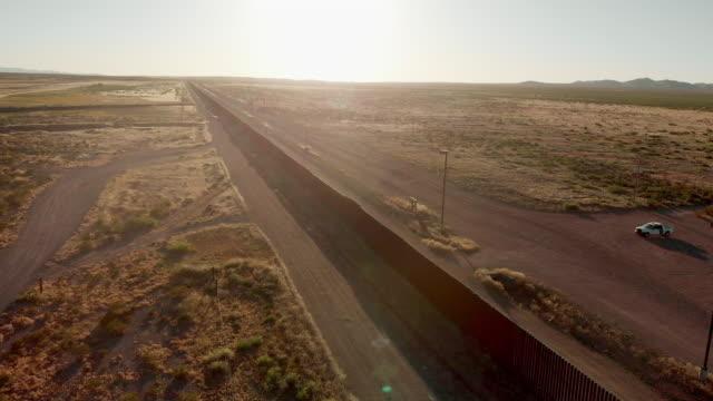 パロマス・チワワとコロンバス・ニューメキシコの交差点での米国とメキシコの国境の壁のドローン4kサンセット映像 - 壁点の映像素材/bロール