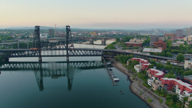 Drone aerial at twilight of the Steel Bridge with two trolleys crossing with flyover of Broadway Bridge and downtown Portland on a summer day video