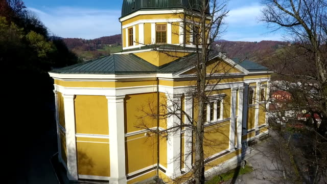 Drone aerial circular view of the Fojnica church tower in Franciscan monastery, video