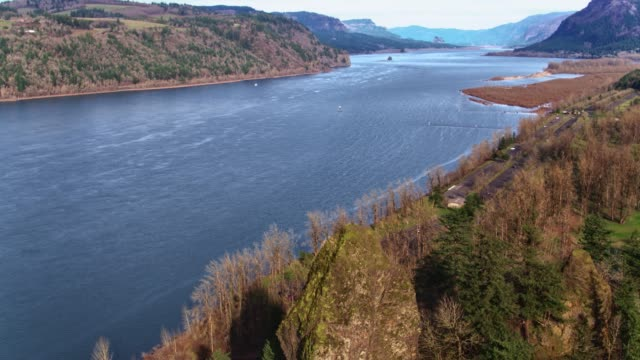 Drone aerial flyover of the towering rock and Columbia River at Rooster Rock State Park in Columbia River Gorge video
