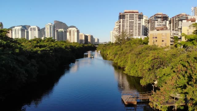Drone aerial Hyperlapse of Marapendi canal in Barra da Tijuca on a summer day, with a boat slowly traveling along river. Tall residential skyscrapers on both sides, with green vegetation video